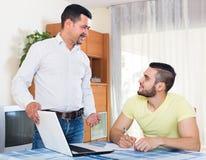 有膝上型计算机的两个人在家 免版税库存图片