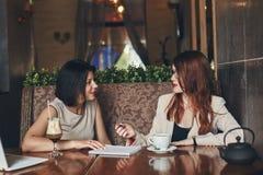 有膝上型计算机的两名年轻微笑的白种人女实业家 咖啡馆的妇女 免版税库存照片