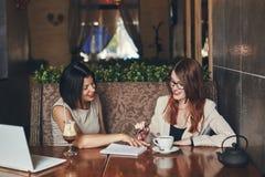 有膝上型计算机的两名年轻微笑的白种人女实业家 咖啡馆的妇女 库存照片
