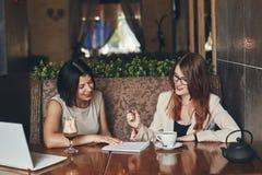 有膝上型计算机的两名年轻微笑的白种人女实业家 咖啡馆的妇女 免版税库存图片