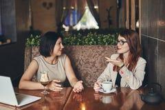 有膝上型计算机的两名年轻白种人女实业家 咖啡馆的妇女 免版税库存照片