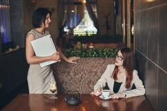有膝上型计算机的两名年轻白种人女实业家 咖啡馆的妇女 库存图片
