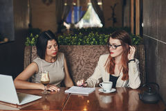 有膝上型计算机的两名年轻白种人女实业家 咖啡馆的妇女 免版税库存图片