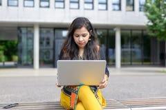 有膝上型计算机的严肃的印地安女孩 图库摄影