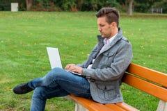 有膝上型计算机的人在公园 免版税图库摄影