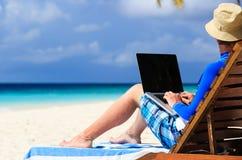 有膝上型计算机的人在热带假期 库存图片