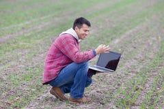 有膝上型计算机的人在领域 免版税库存照片