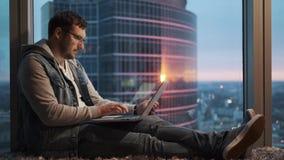 有膝上型计算机的人由窗口坐摩天大楼的一个高地板 股票录像