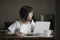 有膝上型计算机的体贴的女孩在厨房 免版税库存图片