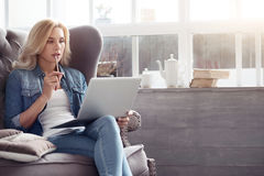 有膝上型计算机的体贴的妇女在家 库存照片
