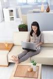 有膝上型计算机的俏丽的女孩在舒适屋子里 库存图片