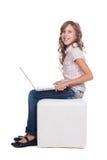 有膝上型计算机的俏丽的兴高采烈的女小学生 免版税库存图片