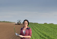 有膝上型计算机的农夫女孩在与拖拉机的领域 免版税图库摄影