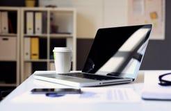 有膝上型计算机的办公室工作场所在反对窗口的木桌上 免版税图库摄影