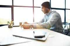 有膝上型计算机的办公室工作场所在反对窗口的木桌上 免版税库存图片