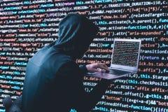 有膝上型计算机的匿名黑客在二进制编码网络安全前面 免版税库存照片
