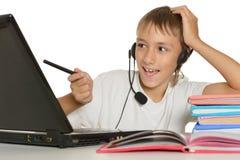 有膝上型计算机的十几岁的男孩 免版税库存照片