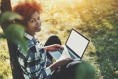 有膝上型计算机的卷曲两种人种的女孩坐草在公园 库存图片