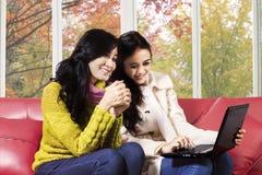 有膝上型计算机的可爱的女孩在家 免版税库存图片