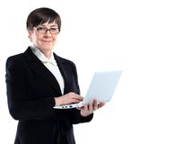 有膝上型计算机的可爱的成熟的商业妇女 图库摄影