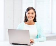 有膝上型计算机的国际学生女孩在学校 库存图片