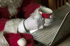 有膝上型计算机的圣诞老人 库存照片