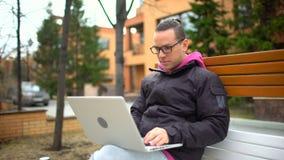 有膝上型计算机的坐在公园的,移动式摄影车射击人 使用有耳机的白种人年轻人膝上型计算机坐长凳在 股票录像