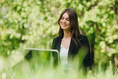 有膝上型计算机的女商人在公园 免版税库存图片