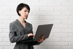 有膝上型计算机的女商人,穿戴在一套灰色衣服在白色墙壁前面摆在 免版税库存图片