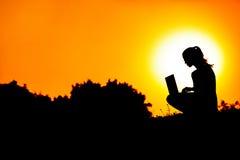 有膝上型计算机的女孩在日落 免版税库存图片