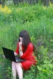 有膝上型计算机的女孩在自然 图库摄影