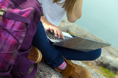 有膝上型计算机的女孩远足者 免版税图库摄影