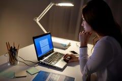 有膝上型计算机的女实业家在夜办公室 库存照片