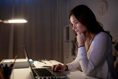 有膝上型计算机的女实业家在夜办公室 免版税库存图片