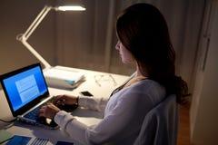 有膝上型计算机的女实业家在夜办公室 库存图片