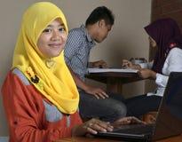有膝上型计算机的女性回教学生 免版税库存照片