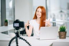 有膝上型计算机的女性在照相机的博客作者和书筛选,并且展示订阅姿态 库存图片