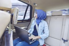 有膝上型计算机的女性穆斯林在汽车里面 免版税库存图片