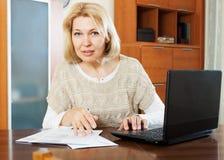 有膝上型计算机的妇女和财政文件在办公室 免版税库存照片