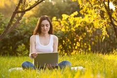 有膝上型计算机的妇女在公园的莲花姿势 库存照片