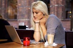 有膝上型计算机的妇女在咖啡馆 免版税库存照片