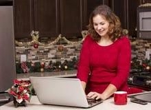 有膝上型计算机的妇女在圣诞节厨房里 库存照片
