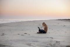 有膝上型计算机的妇女在海滩 免版税库存图片