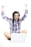 有膝上型计算机的妇女在白色板料在她的床上 免版税库存图片