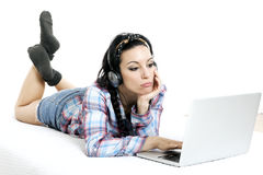 有膝上型计算机的妇女在白色板料在她的床上 库存图片