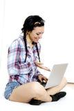 有膝上型计算机的妇女在白色板料在她的床上 库存照片