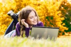 有膝上型计算机的妇女在秋天风景 免版税库存照片
