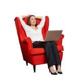有膝上型计算机的妇女在红色椅子 库存图片