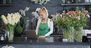 有膝上型计算机的妇女在花卉商店 股票录像
