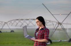 有膝上型计算机的妇女在被灌溉的领域 库存照片
